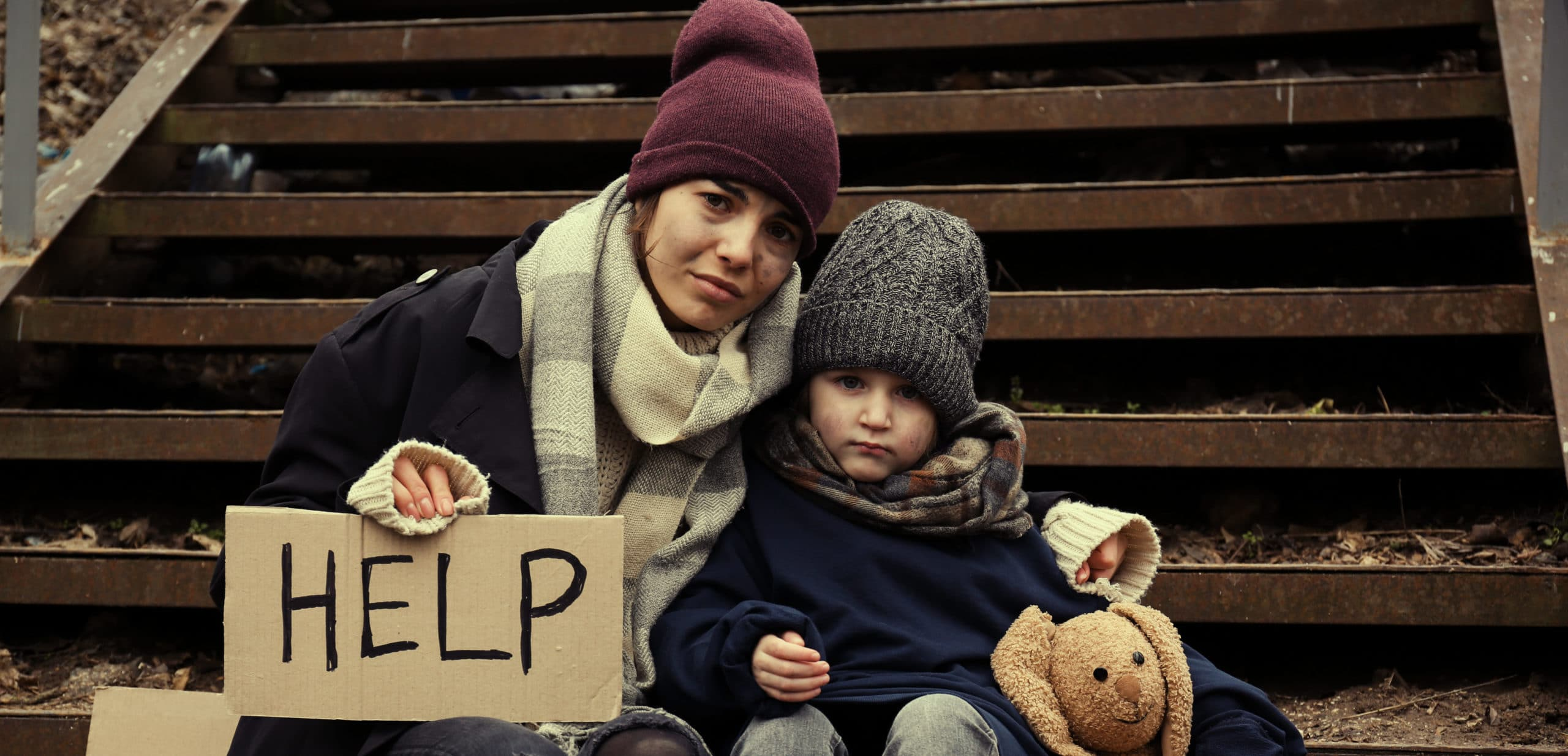 Poor mother and daughter with HELP sign sitting on stairs outdoors
