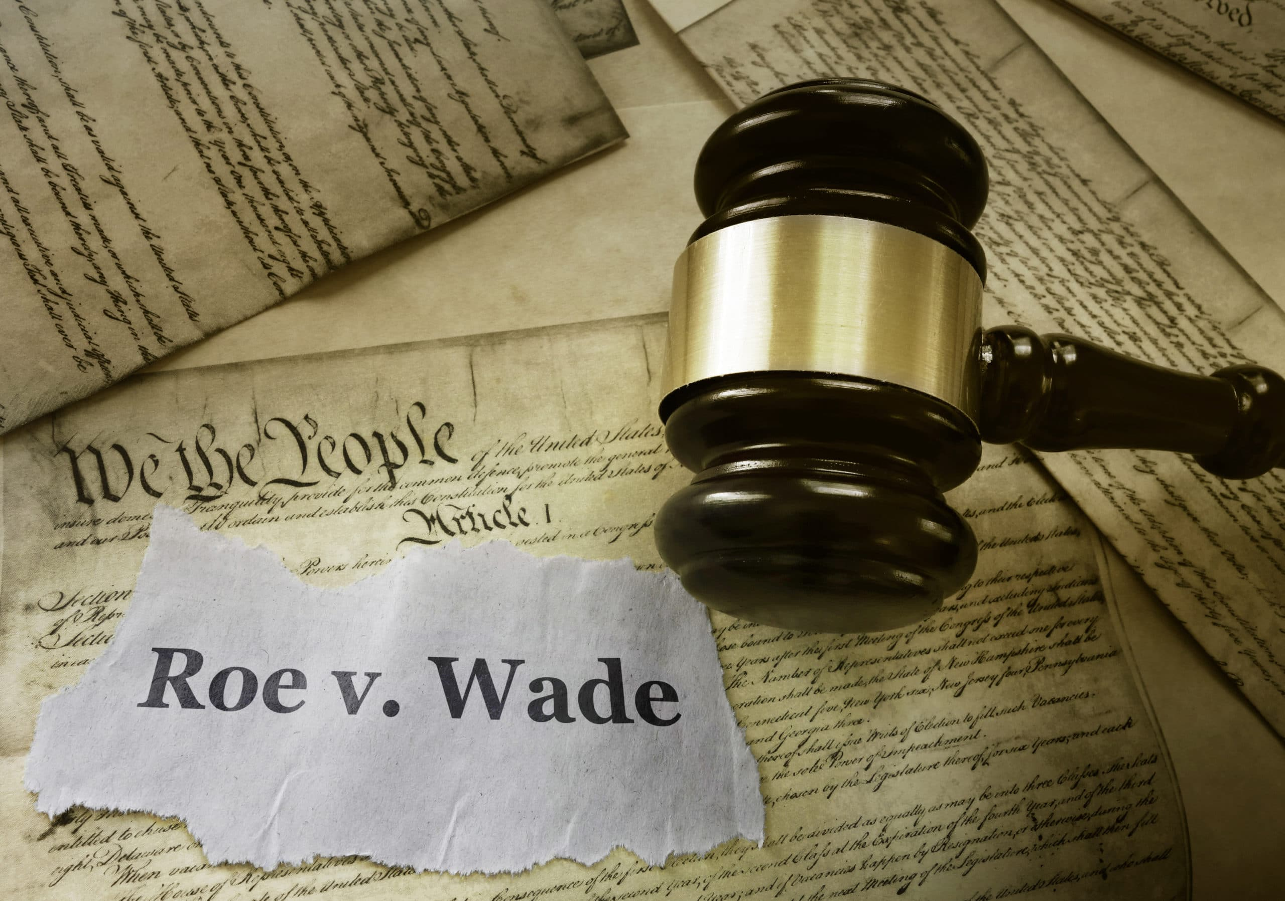 Roe v Wade news headline with gavel on a copy of the United States Constitution legalization of abortion