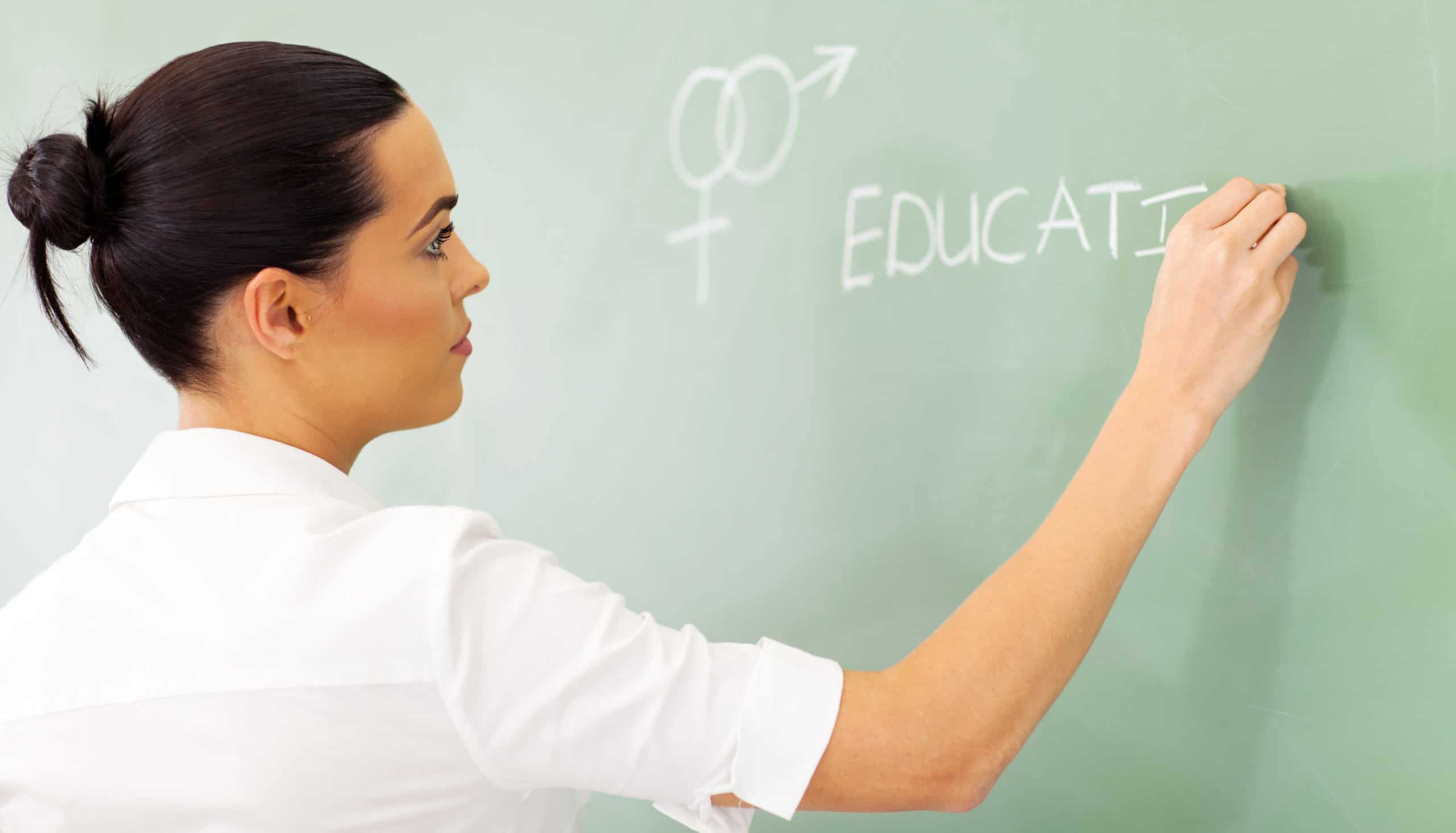 female high school educator writing sex education on chalkboard